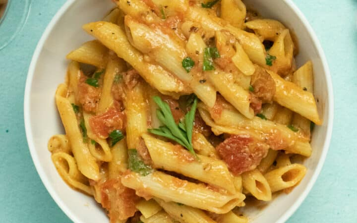 A bowl of penne sits on a blue table