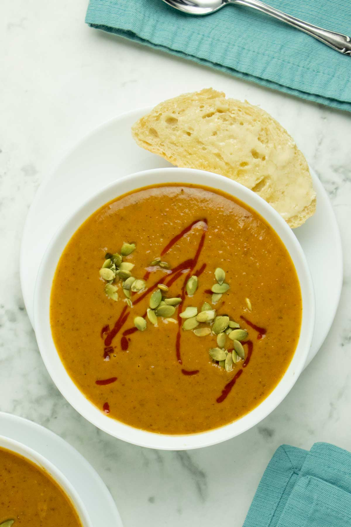 bowl of pumpkin black bean soup with a piece of crusty bread on the side