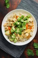 vegan massaman curry tofu in a white bowl on a wooden tabletop