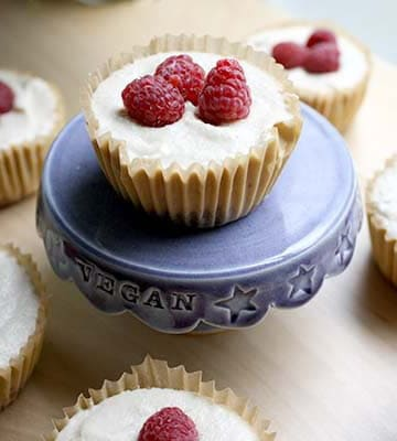 mini vegan cheesecakes topped with raspberries on a serving tray