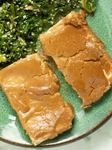 overhead photo of baked tofu with peanut sauce on a plate with ginger kale