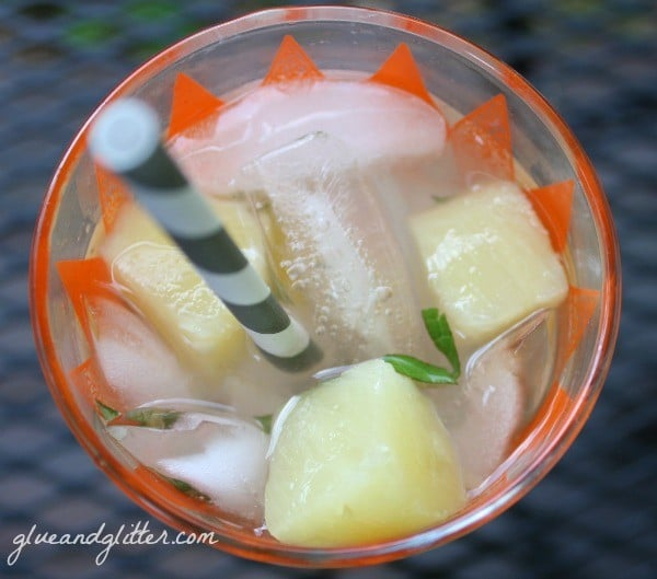 overhead photo of a mojito on ice with pineapple chunks