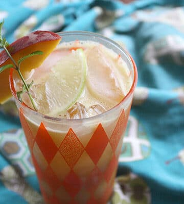 peach mojito in a glass with lime, peach, and min garnish