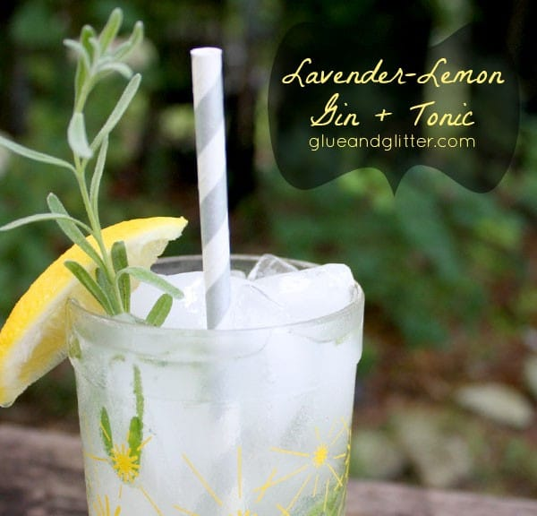 glass of lavender lemon gin and tonic on a picnic table with sprigs of lavender and lemon slices, text overlay