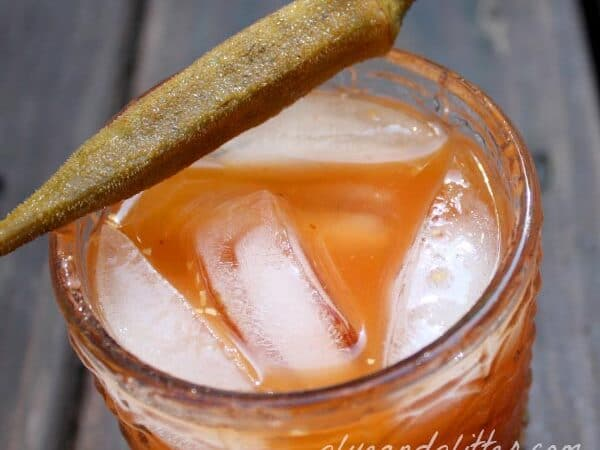 ginger bloody Mary on ice in a glass with pickled jalapeno garnish