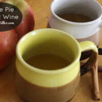 mulled white wine in mugs on a wooden table next to apples and cinnamon sticks