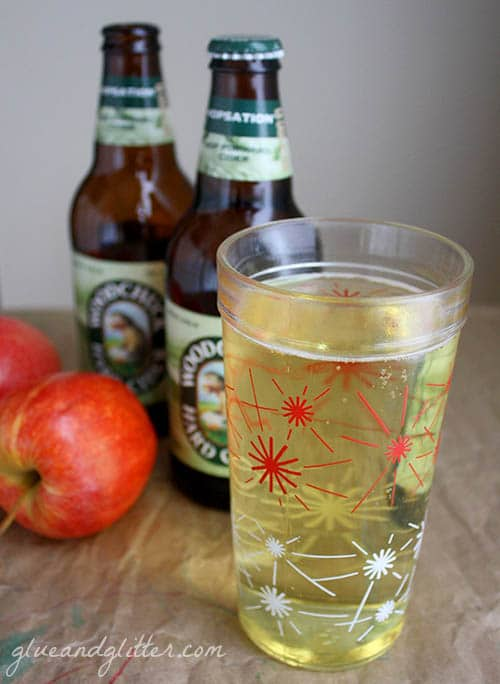 A bottle and a glass of cider on a table