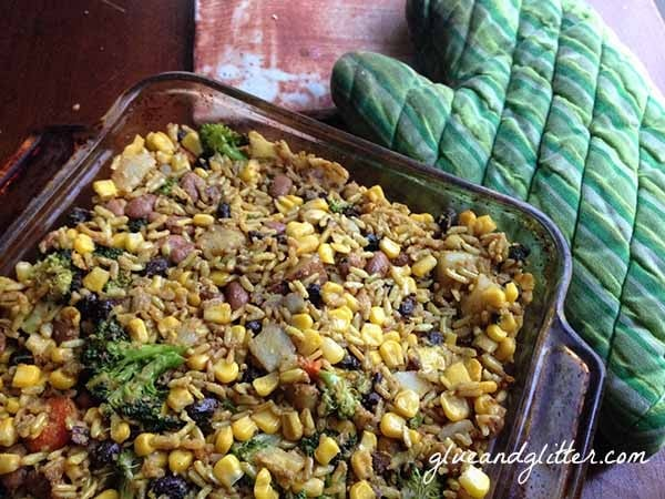 A casserole dish of beans and rice with corn and broccoli