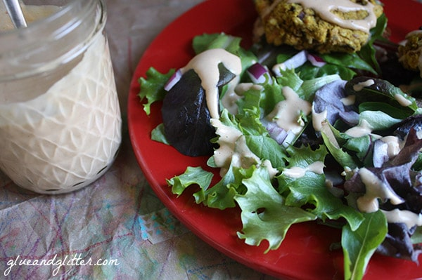 green salad with magical tahini dressing on a red plate. jar of dressing on the side