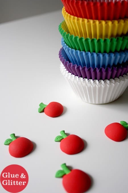 cherry candy on a table next to rainbow cupcake liners