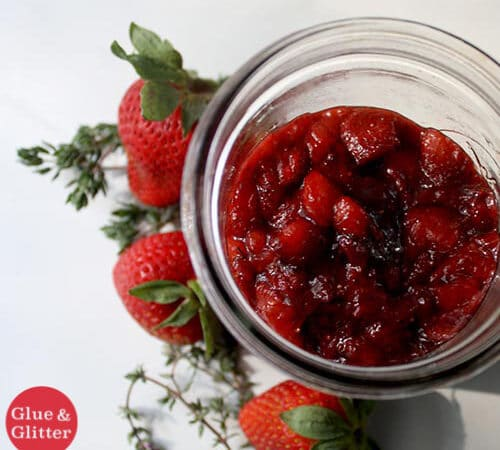 jar of strawberry jam on a white table next to fresh strawberries and thyme
