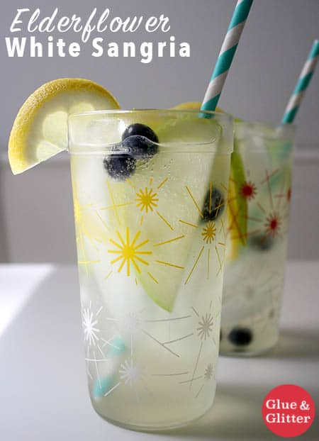 glasses of white wine sangria with blueberries and lemon wedges