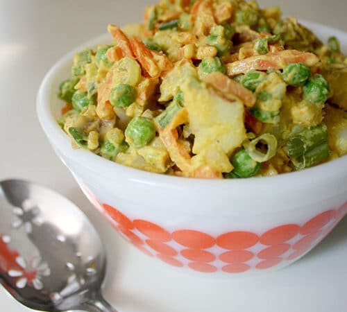 white and orange bowl full of curried potato salad