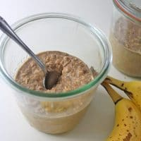 peanut butter and banana overnight oats in a jar next to a bunch of bananas
