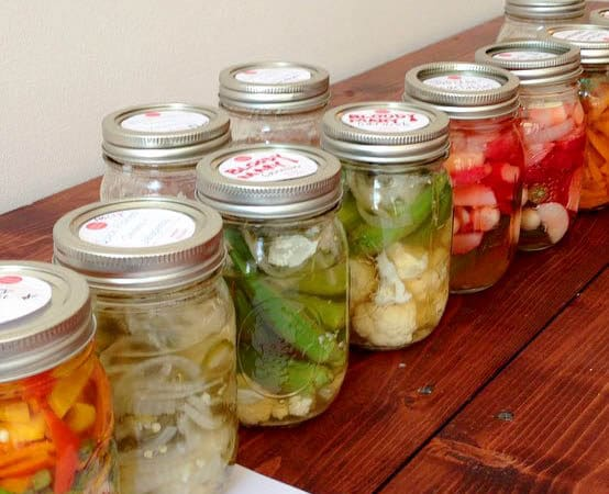 a wooden table covered with with different pickled vegetables in it