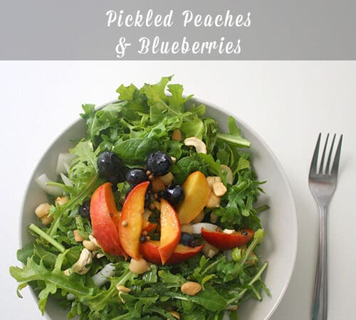 bowls of arugula salad with pickled peaches and blueberries on top