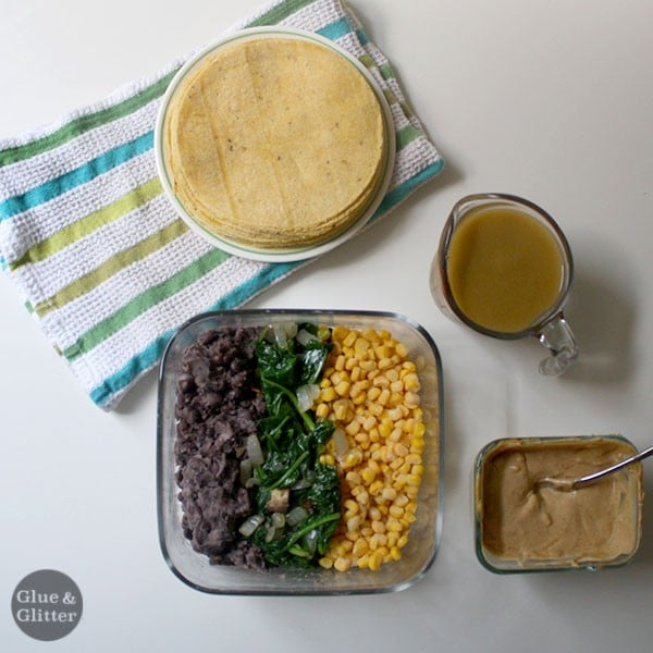 beans, spinach, and corn in a bowl next to cashew cream sauce, green enchilada sauce, and corn tortillas on a white table
