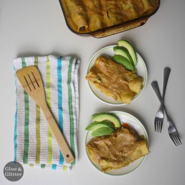 overhead photo of vegan enchiladas on plates next to the baking pan