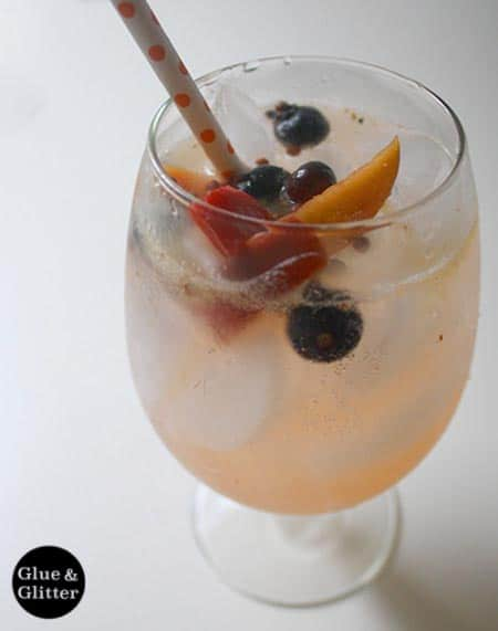 Pickled peaches and blueberries give this homemade white wine cooler recipe a sweet and sour edge.