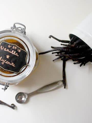 overhead photo of jar of vanilla glycerite next to a jar of vanilla beans