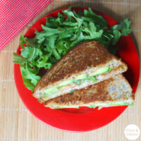 vegan grilled avocado sandwich on a plate next to an arugula salad