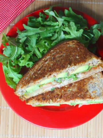 vegan grilled avocado sandwich on a plate next to an arugula salad