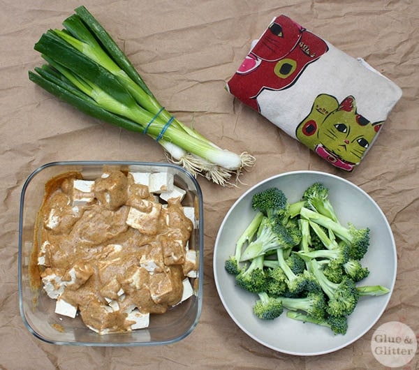 tofu marinating in ginger almond sauce next to a bowl of chopped broccoli and a bundle of green onions