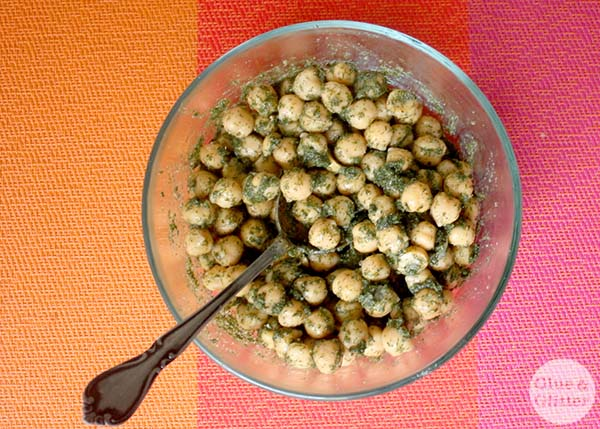 seasoned chickpeas in a glass mixing bowl with a spoon
