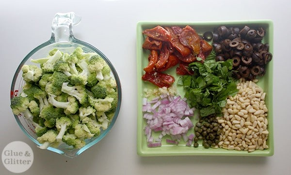 measuring bowl of broccoli next to a tray of sun dried tomatoes, sliced olives, red onion, capers, garlic, and pine nuts