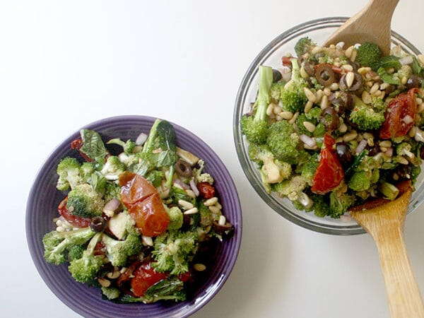 bowls of raw broccoli salad with sun dried tomato on a white table