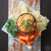 overhead photo of vegan queso in a serving bowl with chips, broccoli, and carrots for dipping