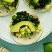 plate of spinach tacos with black beans, pineapple salsa, and sliced avocado