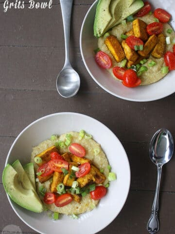 overhead photo of a grits bowl with tofu, tomato, green onion, and avocado slices on a wooden table