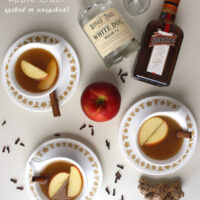 mugs of mulled apple cider on a table next to bottles of white whiskey and Cointreau, text overlay