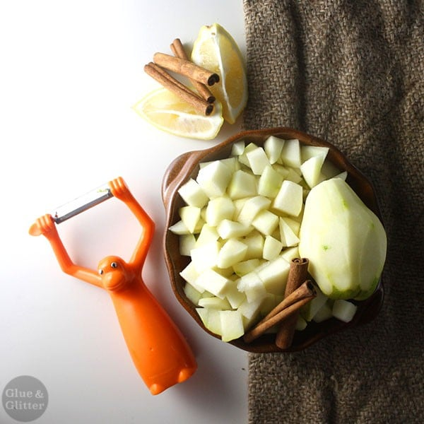 chopped pear in a bowl with cinnamon sticks next to a monkey-shaped vegetable peeler