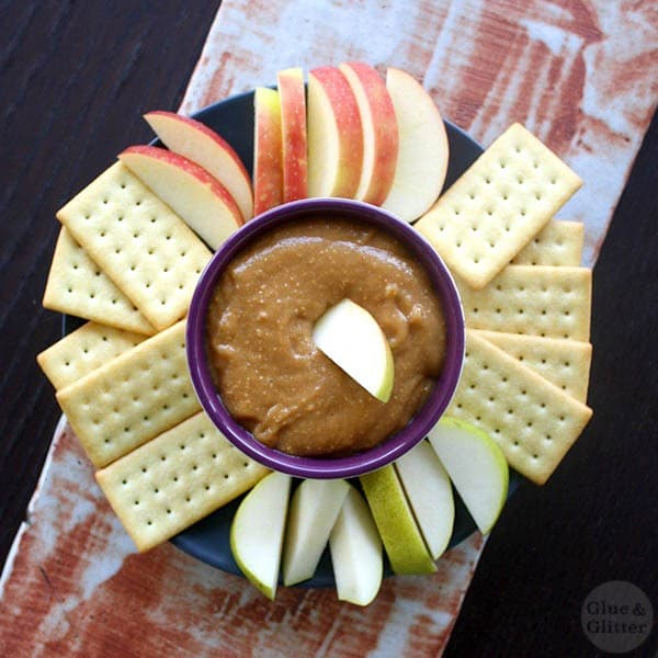 overhead photo of peanut butter dip on a serving platter with apple slices and crackers for dipping