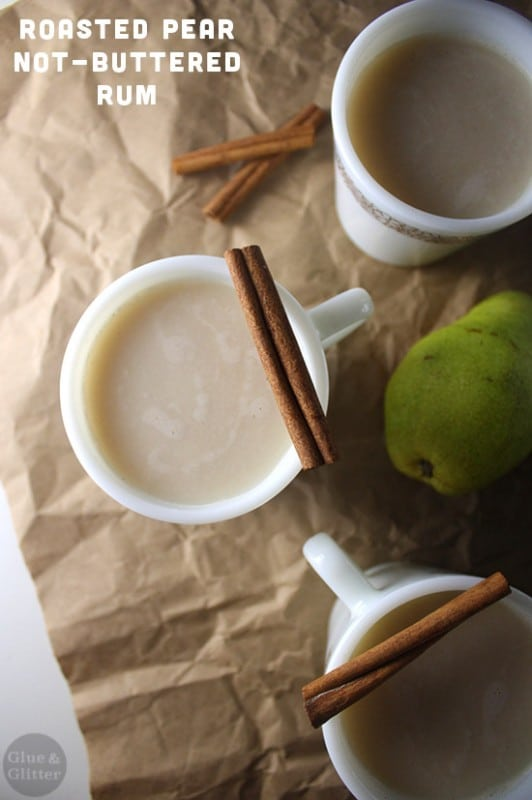 overhead photo of roasted pear vegan buttered rum in mugs with cinnamon stick garnish and pears on the table