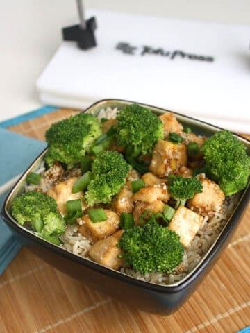 a bowl of sesame tofu on a table with chopsticks next to the EZ Tofu Press