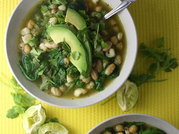 overhead photo of vegan green and white chili in a bowl with sliced avocado and lime garnish