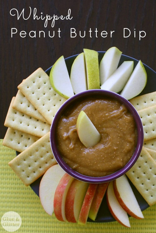 close-up of peanut butter dip on a serving platter with apple slices and crackers for dipping, text overlay