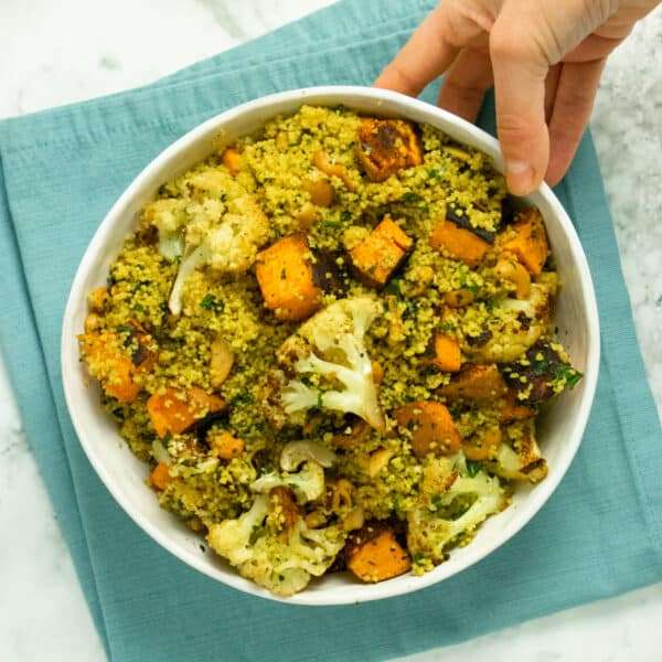 hand placing a bowl of curried couscous salad with roasted vegetables on a table