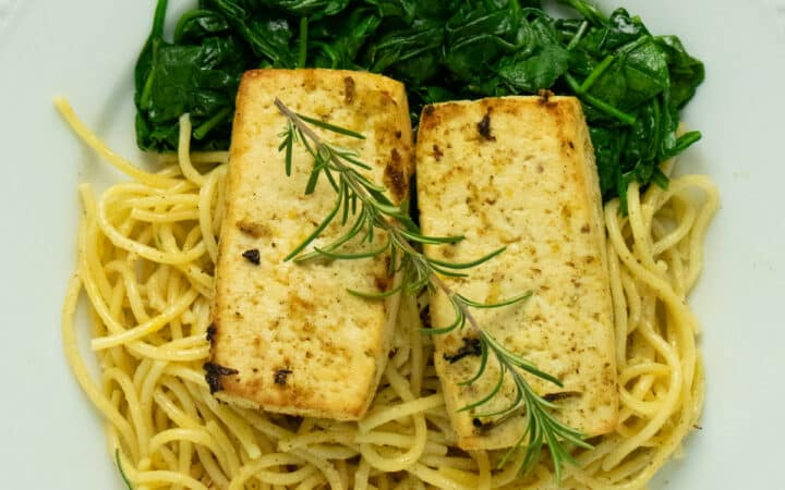 close-up of lemon herb tofu on a white plate served over a bed of spaghetti and spinach
