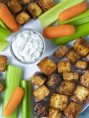 sriracha tofu bites on a serving tray with carrots, celery, and ranch dipping sauce