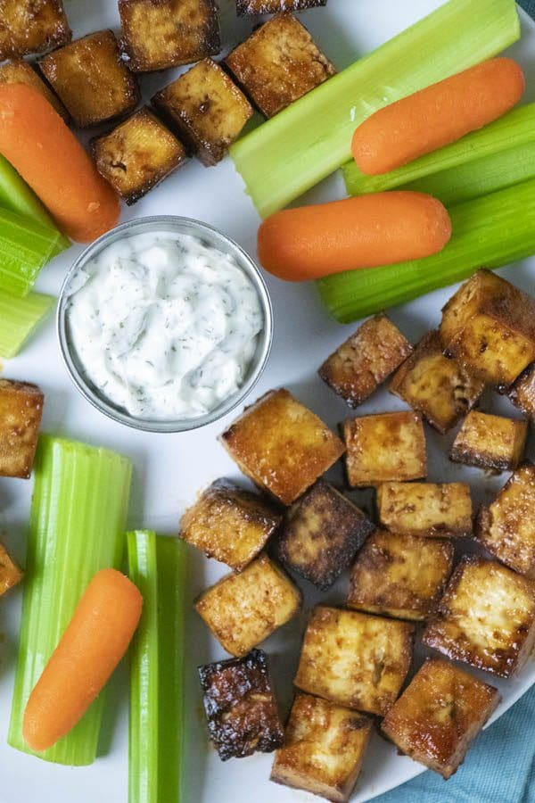 close-up overhead photo of tofu bites on a plate with carrots, celery, and ranch