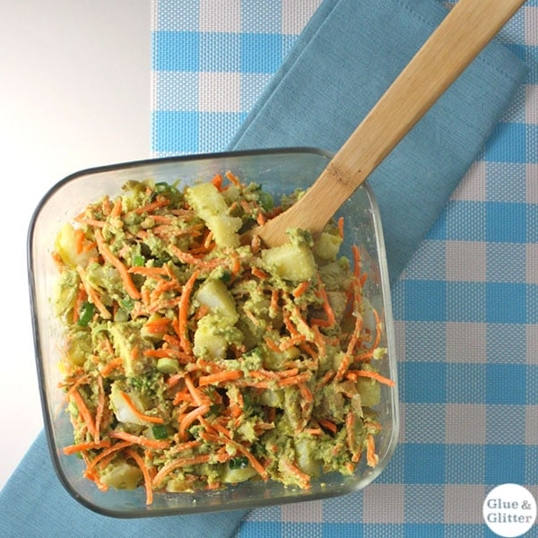 Creamy pesto potato salad with vibrant shredded carrot tossed in a decadent, earthy-green pesto sauce.
