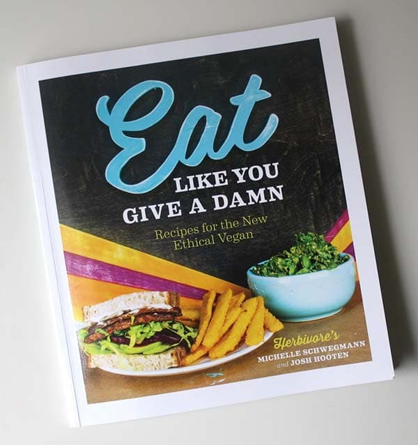 the cookbook, Eat Like You Give a Damn, on a white table