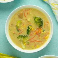 A bowl of vegan corn chowder with broccoli and carrots on a table