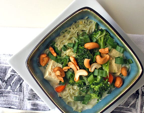 overhead photo of coconut noodle soup wit broccoli, tofu, and cashews