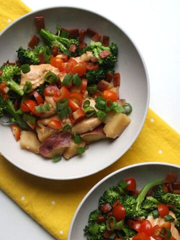 overhead photo of cubed potato topped with broccoli, tomatoes, green onions, and creamy sauce