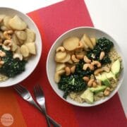 bowl of quinoa with steamed parsnips, massaged kale, sliced avocado, and cashews
